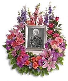 Photo wreath of pink, purple and orange flowers accented with greenery.