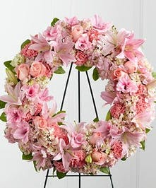 Pastel pink sympathy wreath accented with greenery.