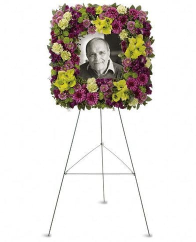 Purple and green flowers in the shape of a wreath, suitable for funeral service.