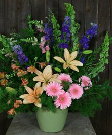 Sympathy basket arrangement of lilies, larkspur, snapdragons and gerbera daisies.