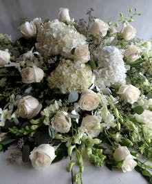 All-white casket spray of hydrangea, roses and dendrobium orchids.