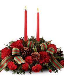 Christmas centerpiece of red roses and carnations, pinecones, and mixed greenery with a holiday ribbon and two taper candles.