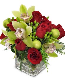 Green orchids, red roses, hypericum and more with ornaments in a glass cube vase.