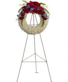 Ring of white flowers topped with red and blue blooms. Patriotic sympathy wreath suitable for a funeral service.