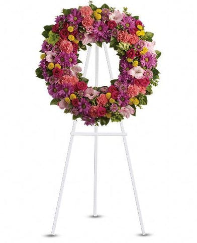 Sympathy wreath in shades of pink, purple and coral accented with greenery.