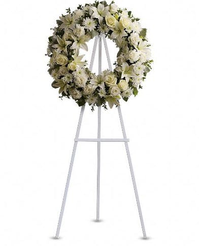 All-white sympathy wreath accented with greenery and presented on an easel.
