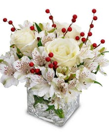 Winter flower arrangement of white roses and alstroemeria with berries in a clear glass cube
