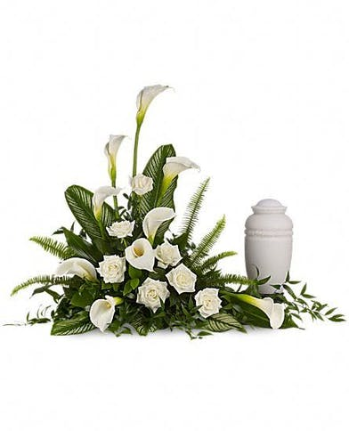 Urn arrangement of all white lilies and roses.