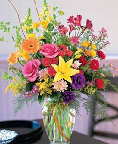Hot pink, yellow and purple flowers in a tall glass vase.