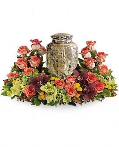 Urn arrangement of orange roses, green hydrangea, and cymbidium orchids.