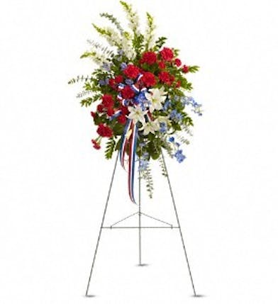 Patriotic standing spray made with red, white and blue flowers and coordinating ribbon.