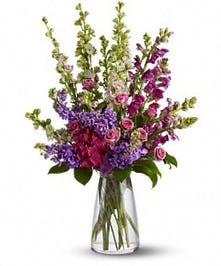 Vased arrangement of larkspur, snapdragons and spray roses.