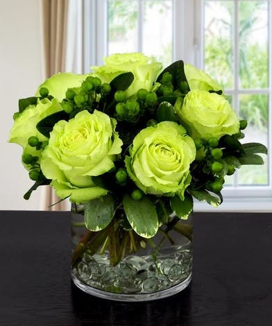 Six green roses and hypericum berries in a glass cylinder vase.