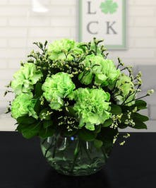 Green carnations in a glass bowl vase.