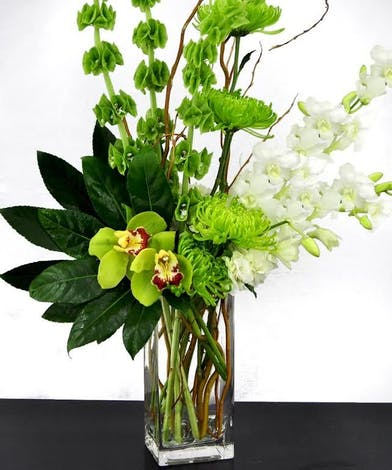 Various flowers in shades of green and white in a tall glass cube vase.