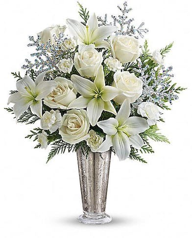 Mercury glass vase filled with white flowers and silver snowflake accents