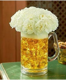 White carnations in a yellow vase shaped like a beer glass.