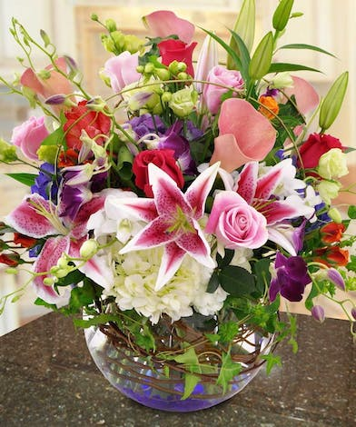Hydrangea, lilies, calla lilies, orchids and more in a glass bubble bowl vase.