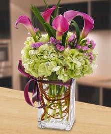 Hydrangea and calla lilies in a tall glass vase.