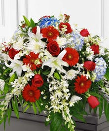 Casket spray made in patriotic red, white and blue flowers.