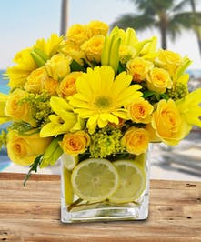 Yellow roses, lilies, gerbera daisies and lemon accent in a clear glass cube vase.