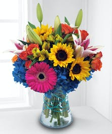 Hot pink, yellow and vibrant blue flowers in a clear glass vase.