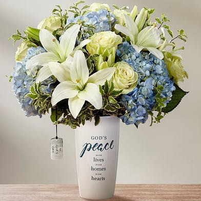 White lilies and blue hydrangea flowers in a white ceramic vase with script that says