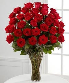36 Beautiful Ecuadorian red roses arranged in a glass vase with assorted greenery.