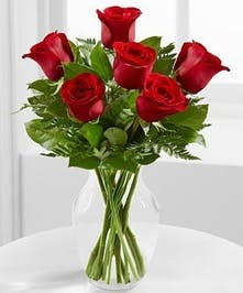 6 red roses with greens in a clear vase.