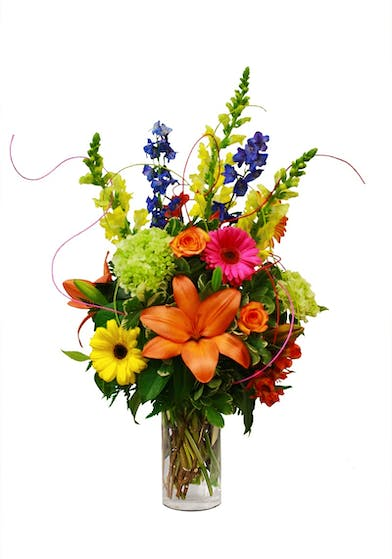 Orange, pink, yellow, green and purple flowers in a clear glass vase.
