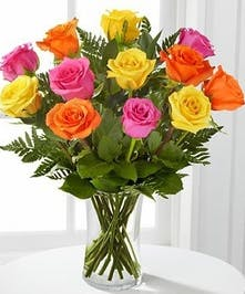 Roses in assorted colors arranged in a clear glass vase.