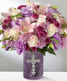 Pink and lavender flowers presented in a purple glass vase accented with a silver cross on the front.