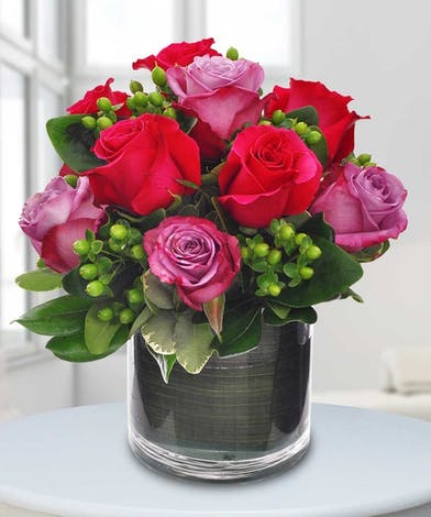 Ten hot pink and lavender roses in a leaf-lined vase.