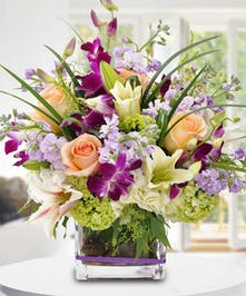 Purple, peach and green flowers in a compact cube vase.