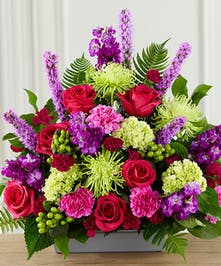 Bright sympathy arrangement of purple and green flowers.