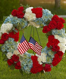 Wreath made of red, white and blue flowers with miniature American flags for a patriotic tribute.