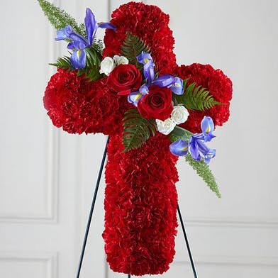 Red floral cross tribute with red, purple and white accent flowers and greenery.