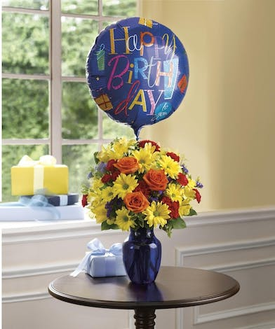 Yellow daisies, alstroemeria, red carnations, purple statice and orange roses in a blue vase with a happy birthday mylar balloon.
