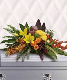 Tropical flower casket spray with greenery.