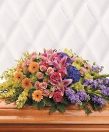 Casket spray of orange, pink, purple and green flowers.