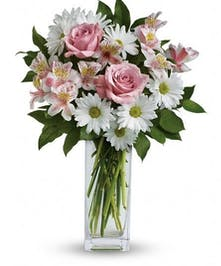 Pink roses, white daisies and Peruvian lilies in a clear glass vase.