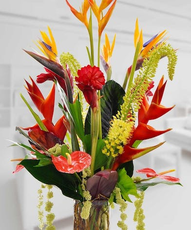 Tropical flowers in a clear glass vase.
