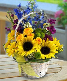 Charming handbasket filled with sunflowers, delphinium, spray roses and stock.