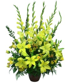 Sympathy arrangement of bright yellow lilies, roses, gladioli and more.