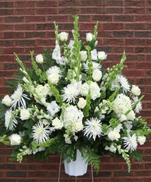 Sympathy arrangement of all white flowers displayed on an easel.