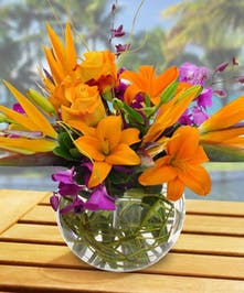 Asiatic lilies, blue and white hydrangea, birds of paradise, orchids and hypericum berries in a glass bubble bowl vase.